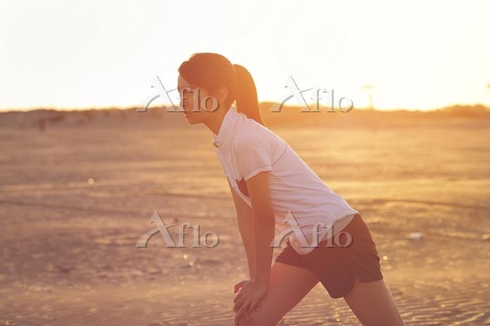 砂浜でストレッチする日本人女の子