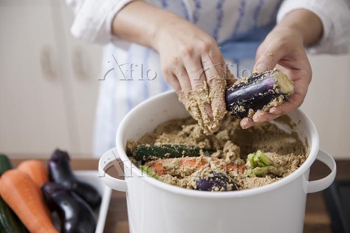 ぬか床に野菜を漬けこむ女性