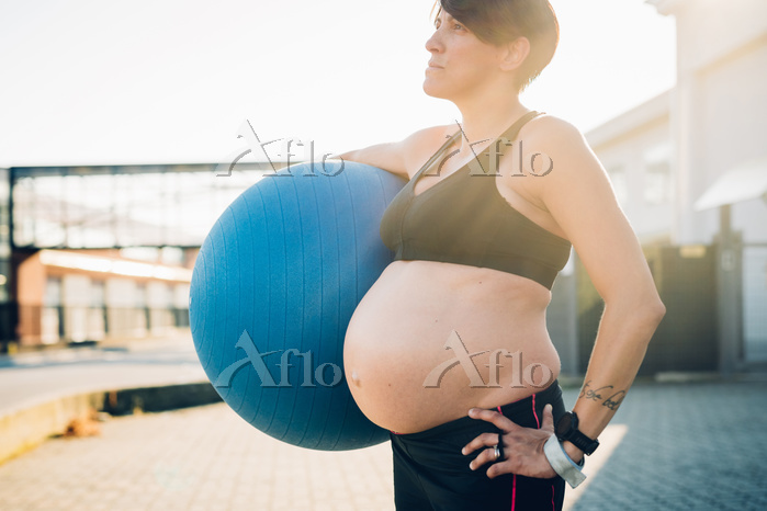 Pregnant woman holding exercis・・・