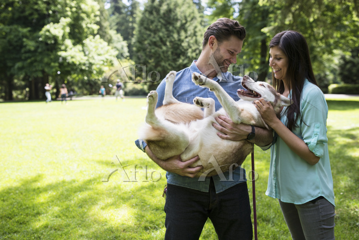 Happy couple playing with dog ・・・