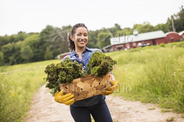 カゴに入っている野菜を持つ女性