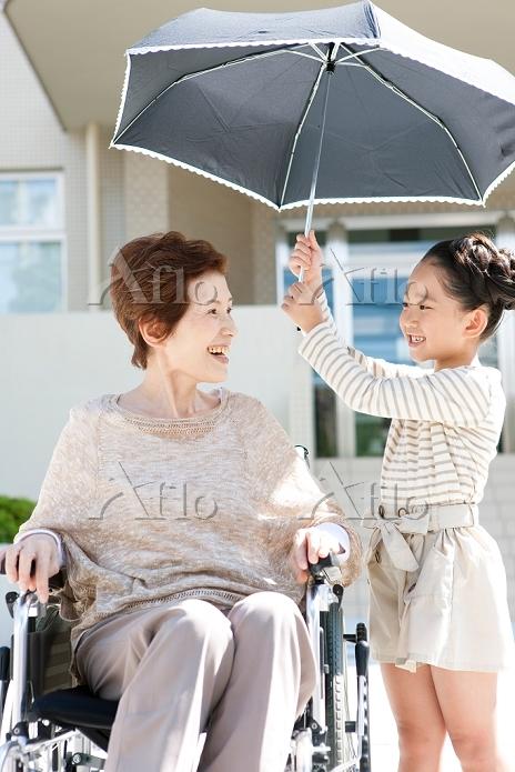 日傘をさす孫と祖母