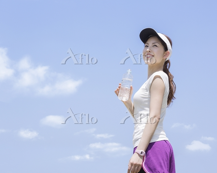 水が入ったペットボトルを持つ女性