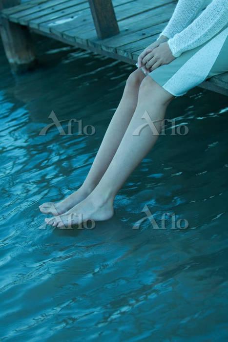 Woman sitting on edge of pier,・・・
