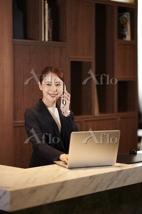 受付をする日本人女性のコンセルジュ
