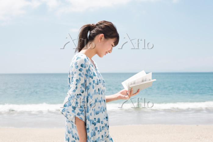 海辺で本を読んでいる女性