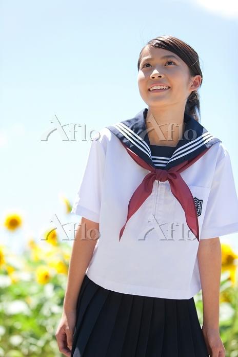笑顔の女子高校生とヒマワリ畑