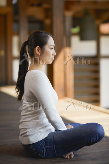 お寺の縁側にいる日本人女性