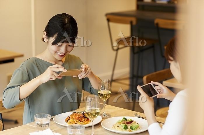 料理をスマホで撮影する日本人女性