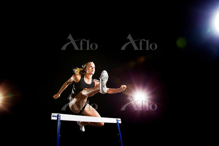 Woman jumping hurdles at night