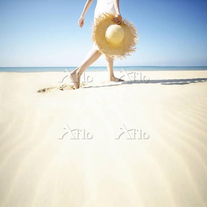 ビーチを散歩する麦わら帽子を持つ女性