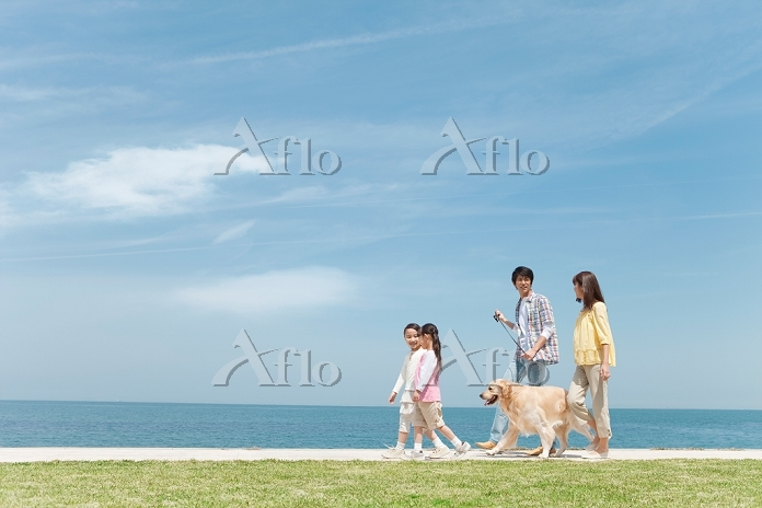 海岸を歩く日本人家族と犬