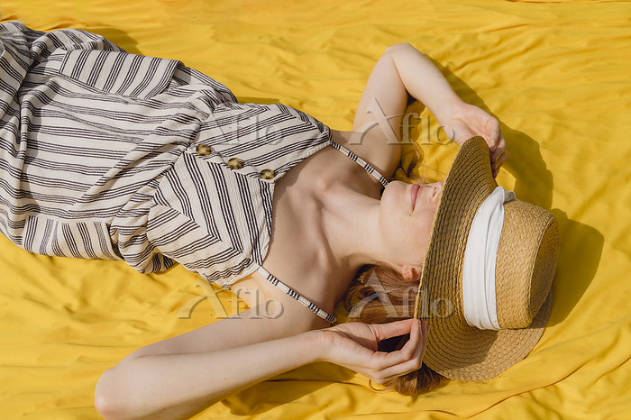 Young woman in sundress holdin・・・