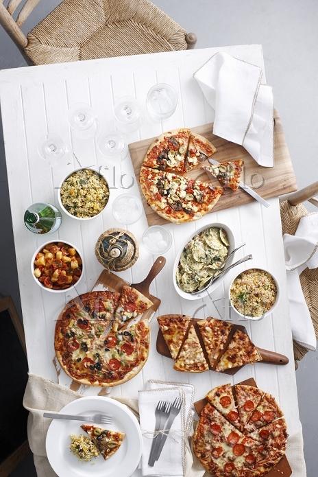 テーブルに並ぶたくさんのピザと料理