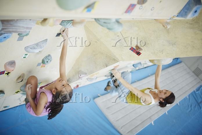 ボルダリングをする女の子と母親