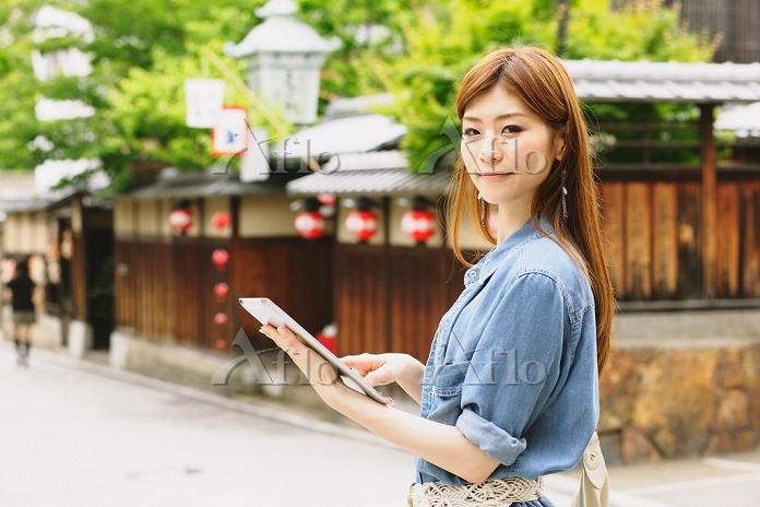 京都の街角でiPadを持つ日本人女性