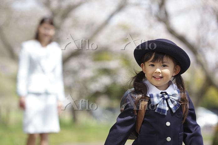 幼稚園児の女の子と見守るスーツのお母さん