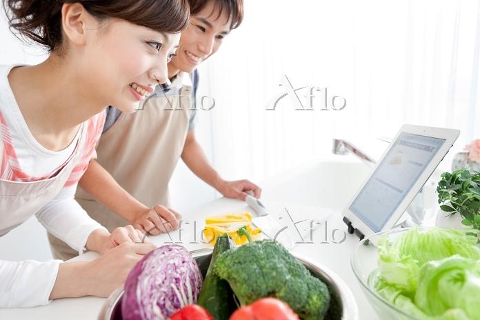 タブレットでレシピを見ているカップル