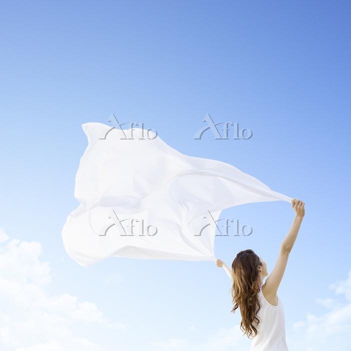 青空の下で布を持って広げる日本人女性