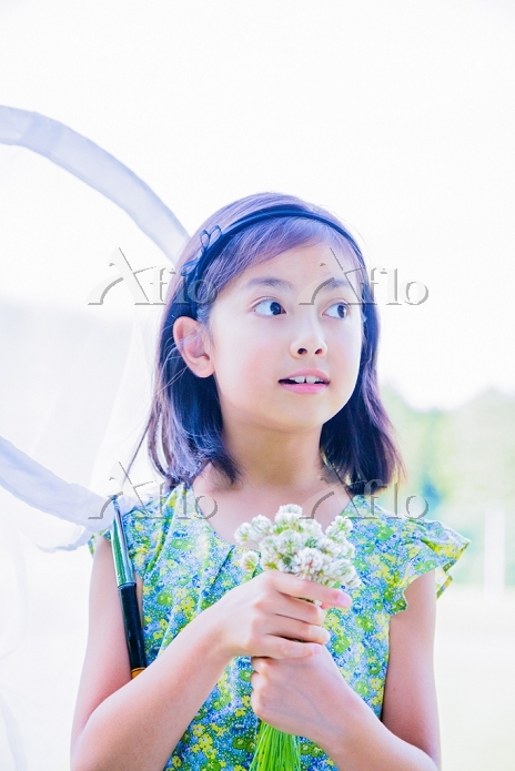 捕虫網とシロツメクサの花束もつ女の子