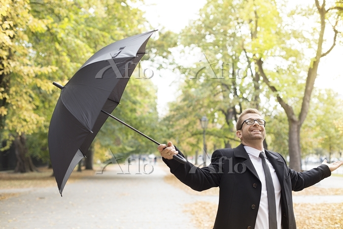 Happy businessman in a park wi・・・