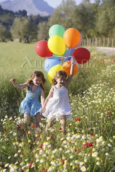 風船を持って草地を走る女の子