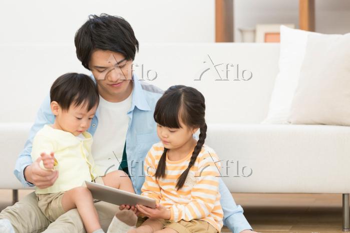 iPadを見ている日本人親子
