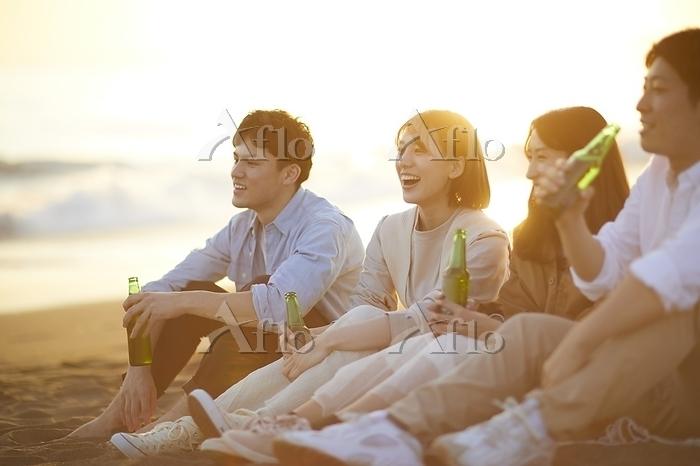 海辺でビールを飲む日本人男女