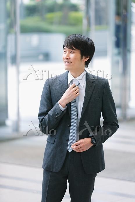 ネクタイを整えるビジネスマン