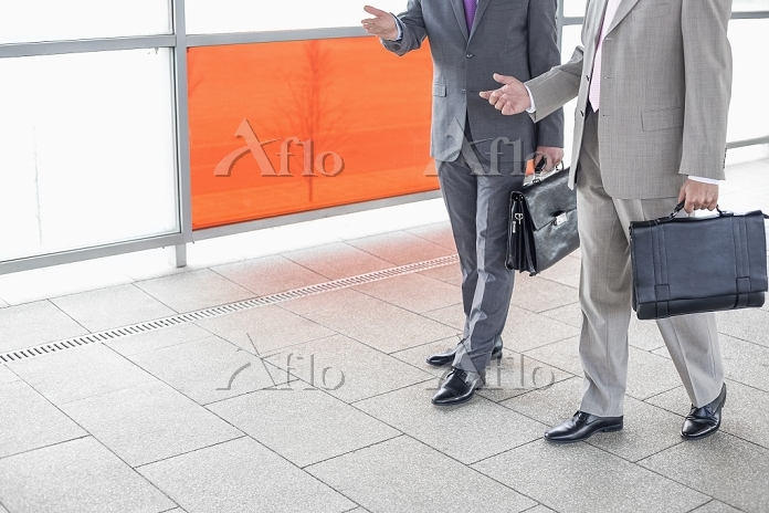 同僚と話ながら歩くビジネスマン