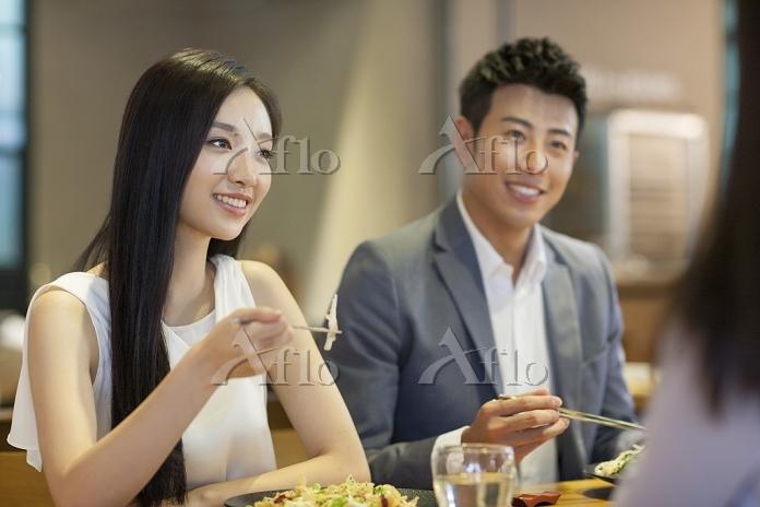 友人と食事する若いカップル