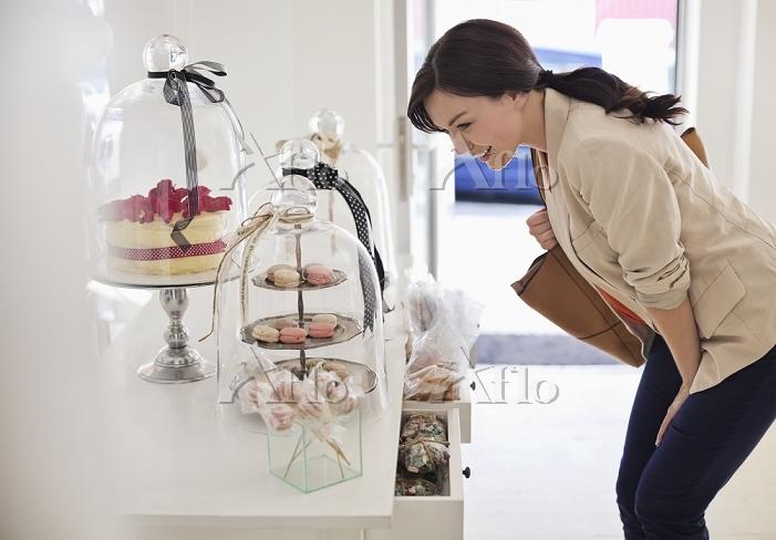 並べられた店頭のお菓子を眺める女性