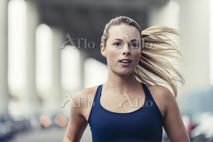 Confident female athlete runni・・・