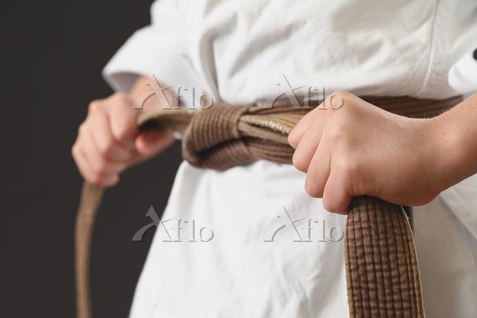 空手着の帯を締める子供