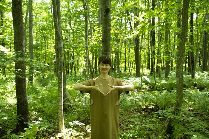 手話で「地球」を表現するミドルの女性