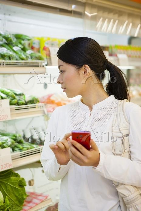 スマートフォンを見て買い物する日本人女性