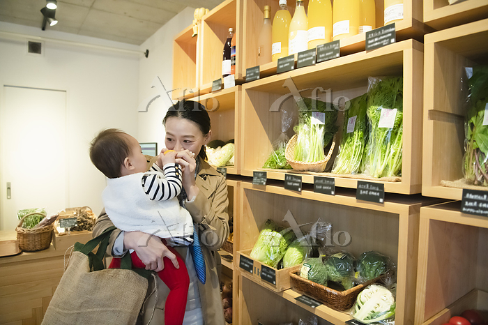 子供連れで有機野菜を選ぶ女性