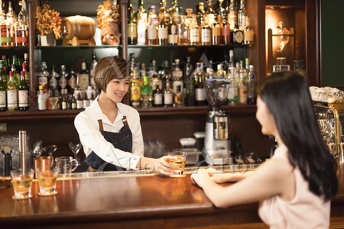 グラスを差し出す店員と女性客