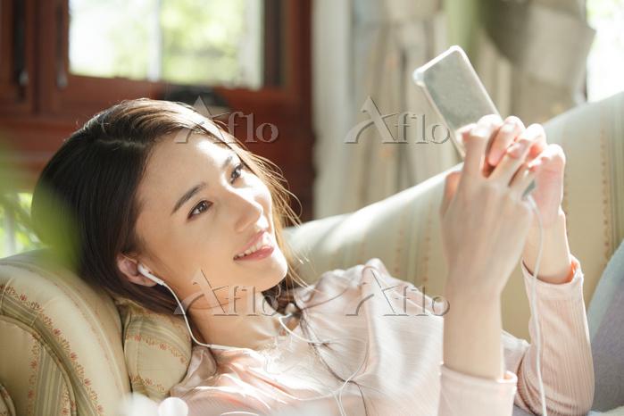ソファでスマートフォンを見る女性