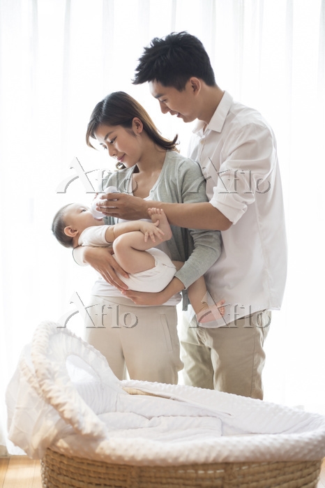 Young parents feeding baby