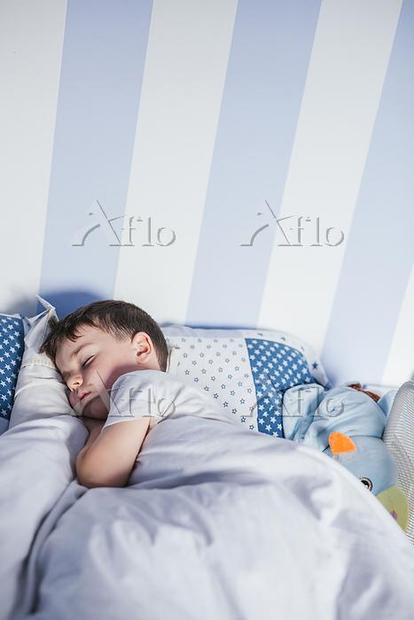 Little boy sleeping on bed in ・・・