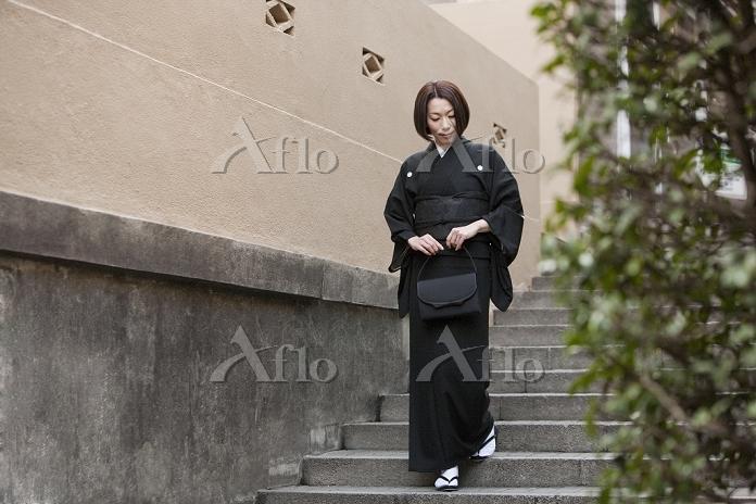 階段を下りる喪服姿の女性
