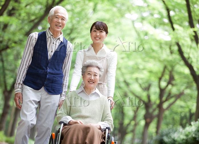 森林浴をするシニア夫婦と介護士
