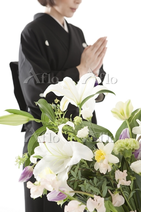 喪服姿で合掌する日本人女性と祭壇の花