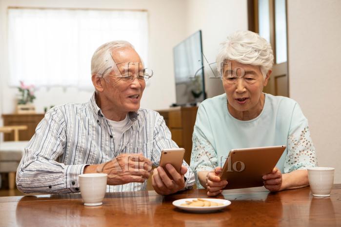 スマホとタブレットを操作する日本人シニア夫婦