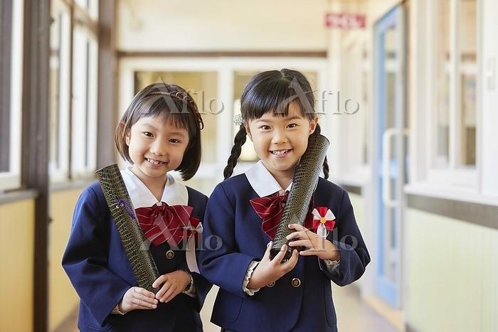 筒を持つ笑顔の幼稚園児の女の子