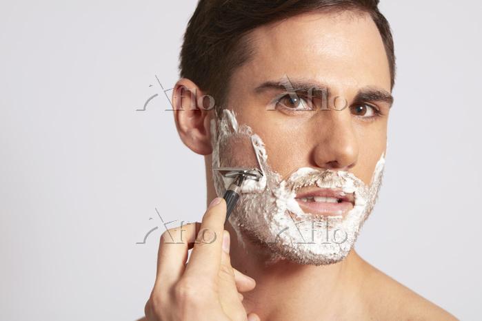 Mid adult man applying shaving・・・