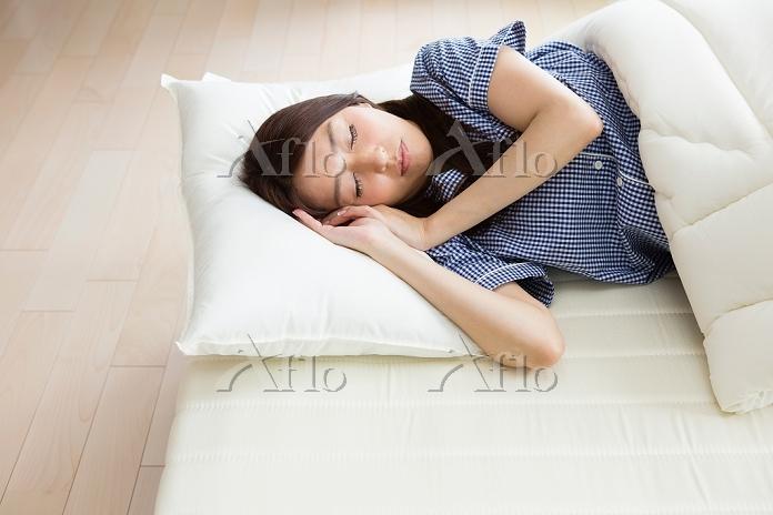 ベッドで眠る日本人女性
