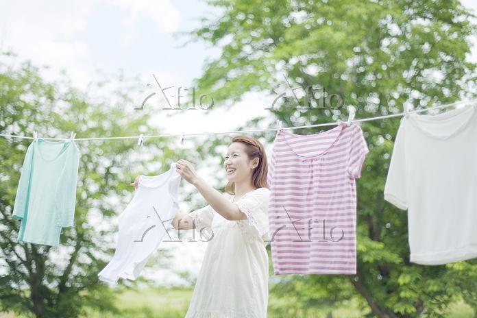 笑顔で洗濯物を干す若い日本人女性