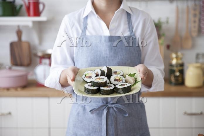調理した巻き寿司の皿を持つ女性